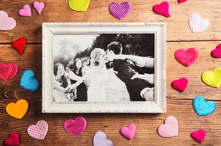 photo frame: Picture frame with wedding photo. Studio shot on wooden background. Stock Photo