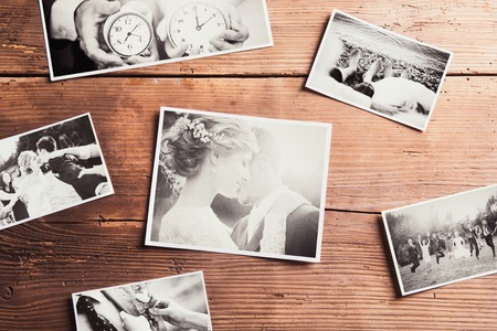 Wedding photos laid on a table. Studio shot on wooden background. Archivio Fotografico