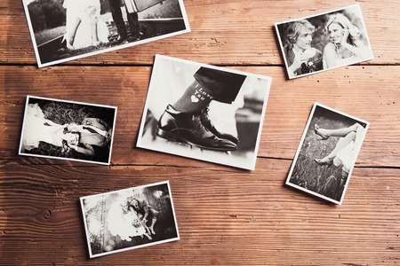 outdoor photo: Wedding photos laid on a table. Studio shot on wooden background. Stock Photo