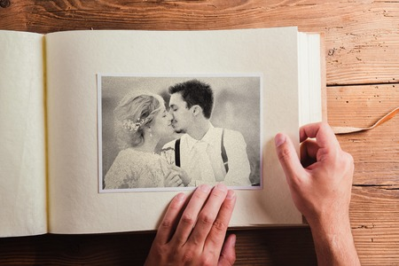 album: Picture of bride and groom in photo album. Studio shot on wooden background.