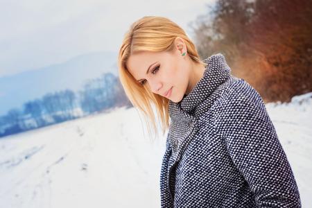 cabello rubio: Mujer rubia hermosa en abrigo gris en la naturaleza de invierno