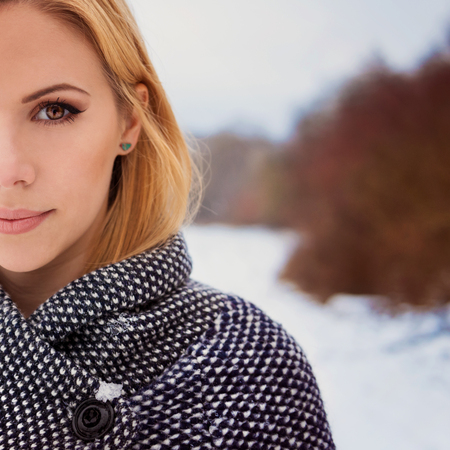 up close: Beautiful blond woman in gray coat in winter nature