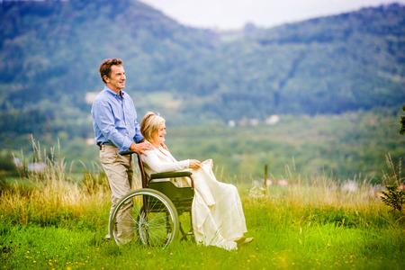 ancianos caminando: Hombre mayor con la mujer en silla de ruedas fuera en la naturaleza
