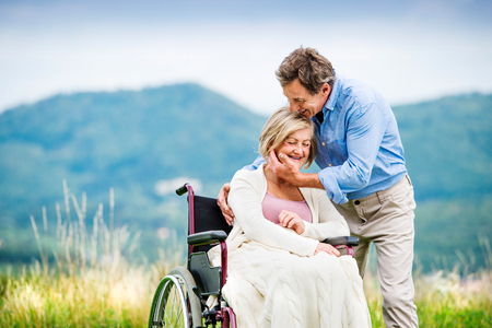 wheelchair woman: Senior man with woman in wheelchair outside in nature Stock Photo