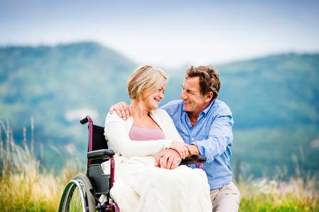 persona en silla de ruedas: Hombre mayor con la mujer en silla de ruedas fuera en la naturaleza