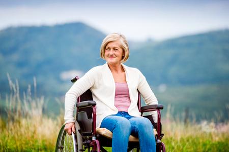 silla de ruedas: Mujer mayor en silla de ruedas fuera en la naturaleza Foto de archivo