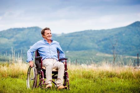 persona mayor: Hombre mayor en silla de ruedas fuera en la naturaleza