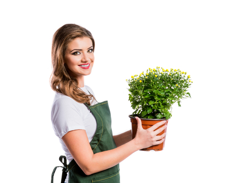 flower pot: Beautiful young woman in mustard sweater. Studio shot on white background. Stock Photo