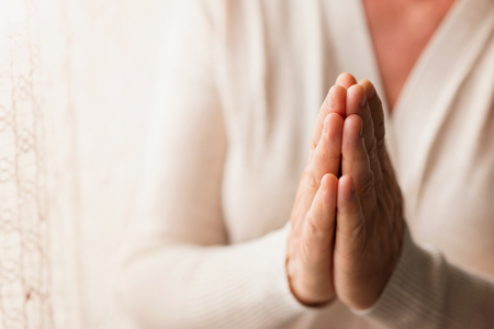 christian women: Hands of an unrecognizable woman in white cardigan praying Stock Photo