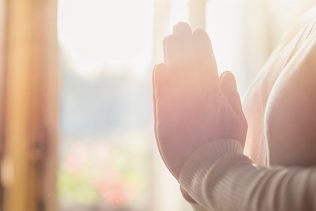 Hands of an unrecognizable woman standing by the window and praying Stock Photo