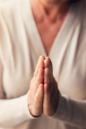 Hands of an unrecognizable woman in white cardigan praying Stock Photo