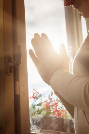 gods love: Hands of an unrecognizable woman standing by the window and praying Stock Photo