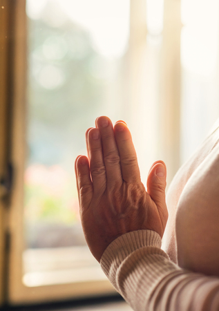 intercede: Hands of an unrecognizable woman standing by the window and praying Stock Photo