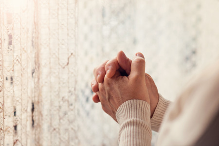 Hands of an unrecognizable woman standing by the window and praying Standard-Bild
