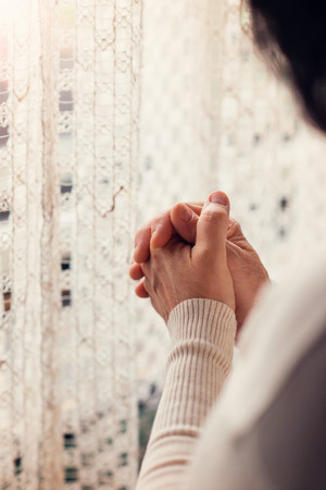 thanksgiving adult: Hands of an unrecognizable woman standing by the window and praying Stock Photo
