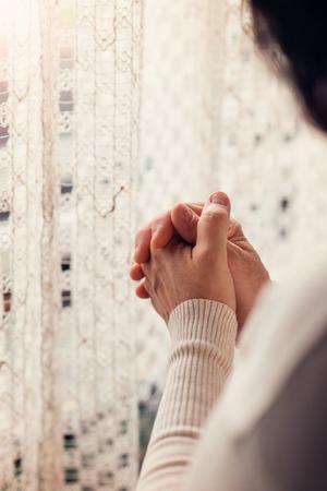 mujeres orando: Manos de una mujer irreconocible de pie junto a la ventana y la oración
