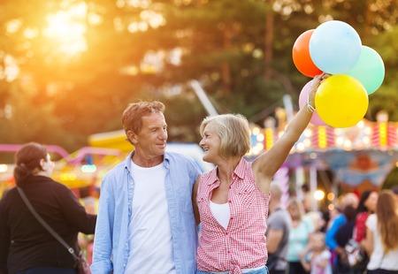 tercera edad: Pares mayores que tienen un buen rato en el parque de atracciones
