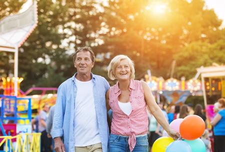 ancianos caminando: Pares mayores que tienen un buen rato en el parque de atracciones