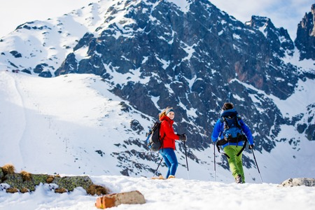 trekking pole: Young couple hiking outside in sunny winter mountains Stock Photo