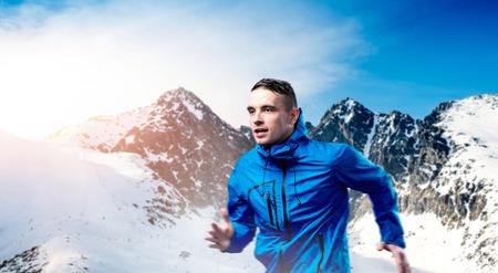 Young man jogging outside in sunny winter mountains