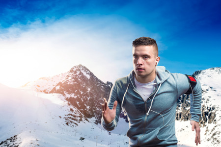 man power: Young man jogging outside in sunny winter mountains