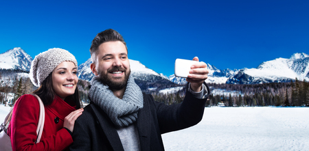 wife and husband: Beautiful couple taking selfie on a walk in mountains