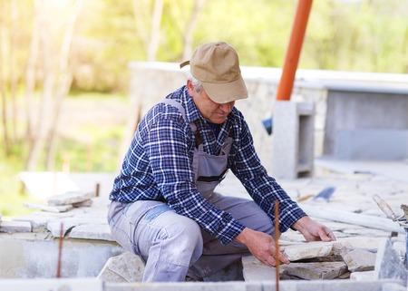 checked shirt: Senior man  in checked shirt laying a stone path
