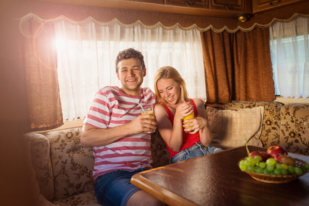 tomando jugo: Beautiful young couple sitting in a camper van on a summer day