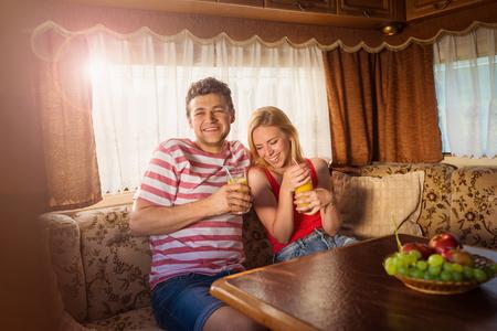 tomando jugo: Pareja joven hermosa que se sienta en una caravana en un día de verano