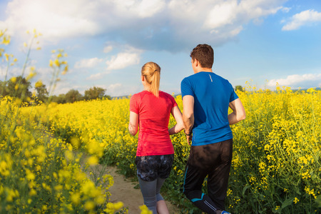 Young couple running outside in spring canola field