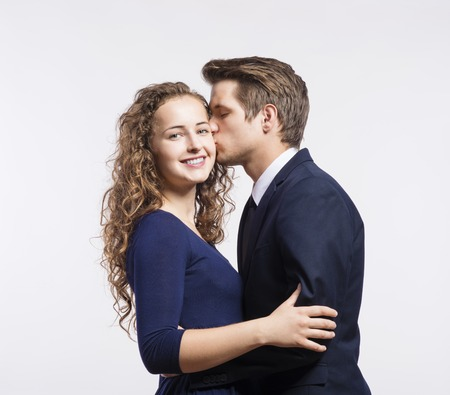 hair style: Beautiful young hipster couple kissing on white background Stock Photo