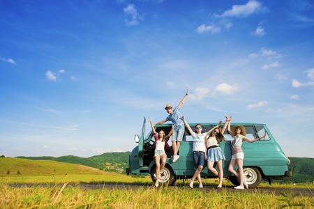 road: Young hipster friends on road trip on a summers day Stock Photo
