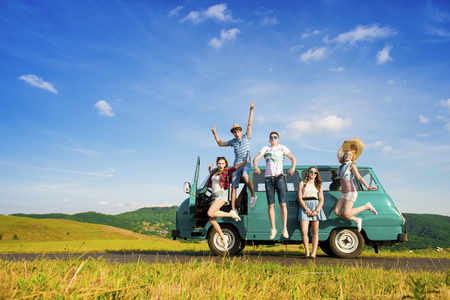 road travel: Young hipster friends on road trip on a summers day Stock Photo