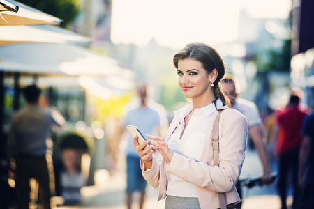 woman business suit: Attractive young business woman with smart phone in the city Stock Photo