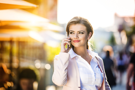 Attractive young business woman with smart phone in the city Stock Photo