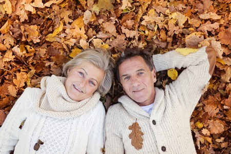 Active seniors lying on the ground in colorful autumn leaves.