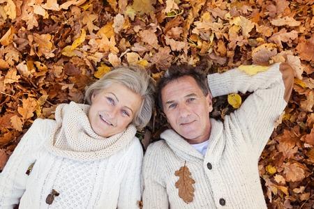 tercera edad: Mayores activos yacen en el suelo en hojas de oto�o de colores.