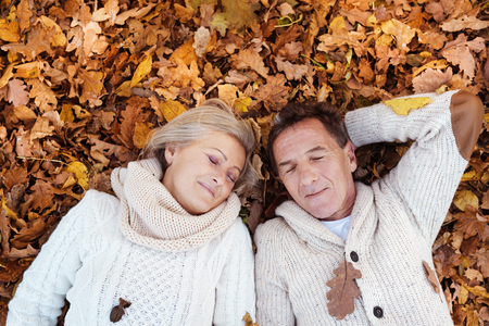 hojas antiguas: Active seniors lying on the ground in colorful autumn leaves.