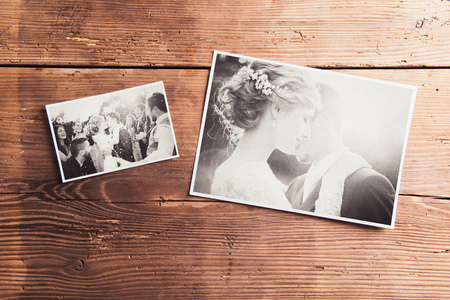 black and white image: Wedding photos laid on a table. Studio shot on wooden background. Stock Photo