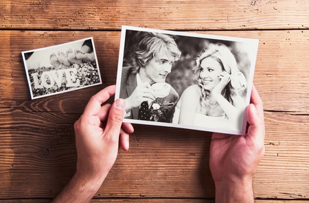 retro lady: Wedding photos laid on a table. Studio shot on wooden background. Stock Photo