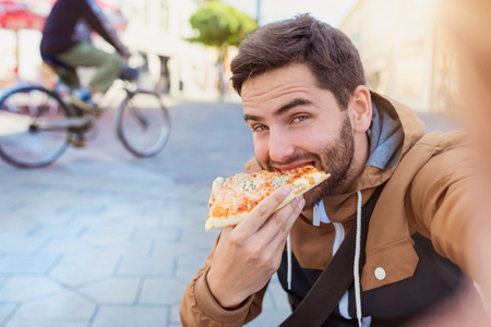 Gut aussehender junger Mann isst ein Stück Pizza draußen auf der Straße Standard-Bild
