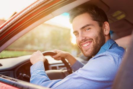 Apuesto joven en una camisa azul que conduce un coche