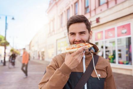personas en la calle: Apuesto joven comer una rebanada de pizza al aire libre en la calle