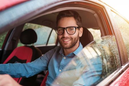 personas sentadas: Apuesto joven en una camisa azul que conduce un coche