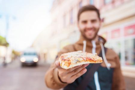 bel homme: Beau jeune homme de manger une tranche de pizza � l'ext�rieur sur la rue