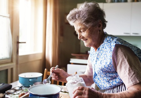 on hands: Senior woman baking pies in her home kitchen.  Measuring ingredients.