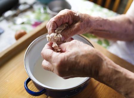 Altos empanadas hornada de la mujer en su cocina en casa. La adición de la levadura en la leche.