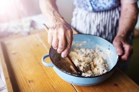 年配の女性は彼女の家の台所でパイを焼きます。 成分を混合します。 写真素材