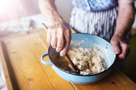 Senior woman baking pies in her home kitchen.  Mixing ingredients. Stock Photo - 46450140
