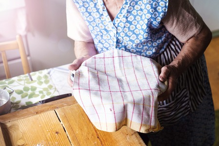 making up: Senior woman baking pies in her home kitchen. Letting yeast dough stand to rise Stock Photo